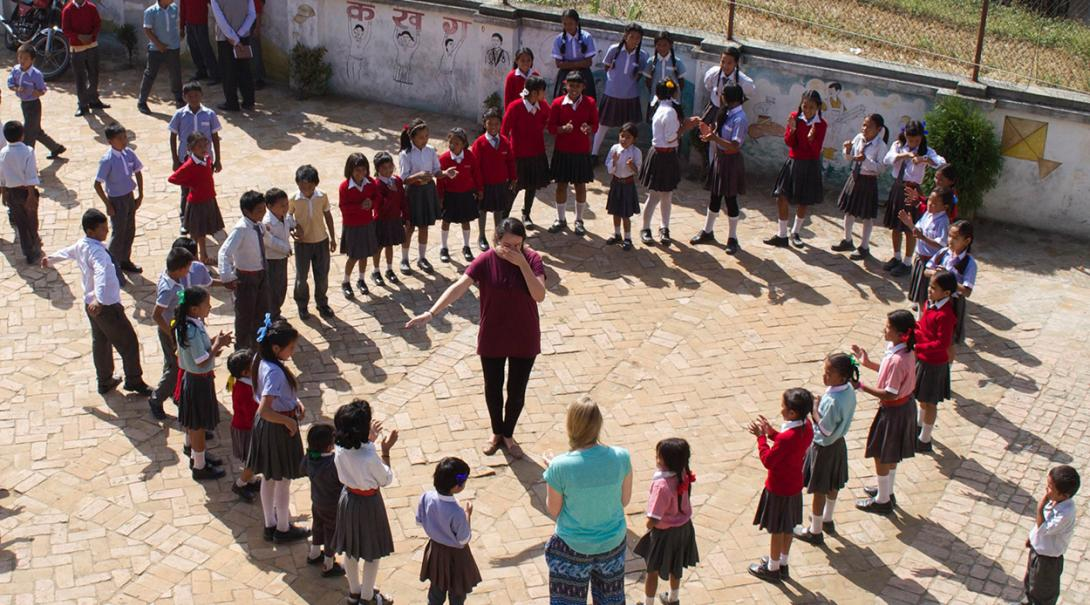 Youth development volunteer playing a game with the students in Nepal